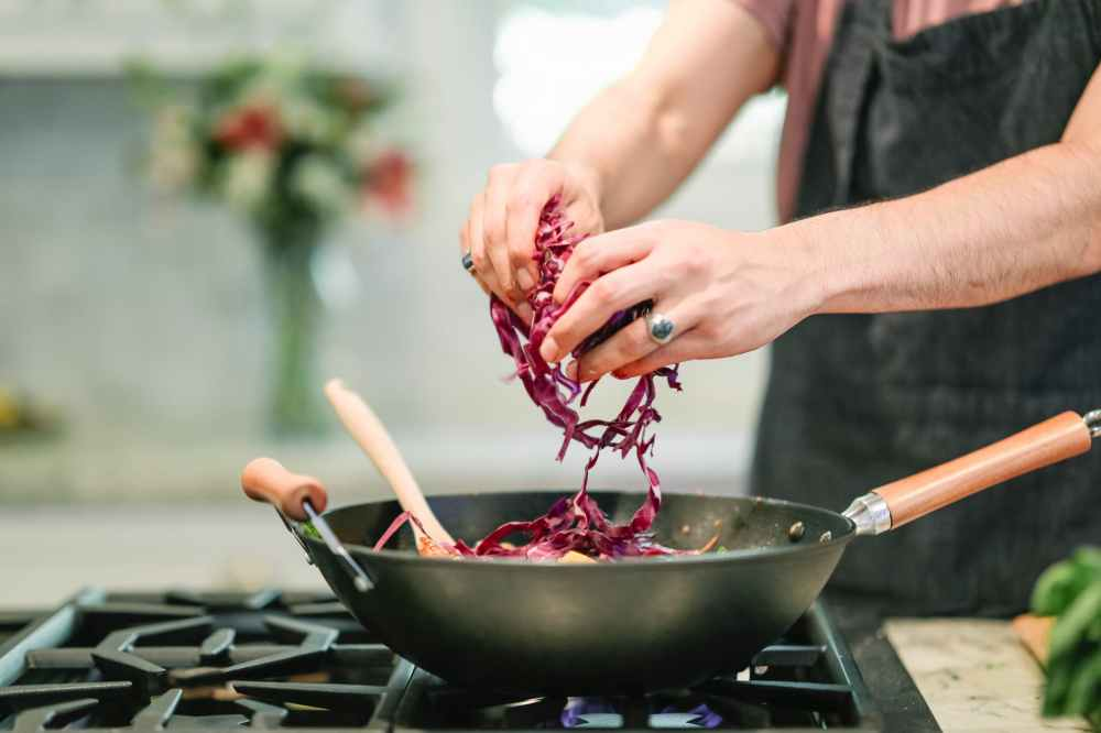 person cooking red cabbage