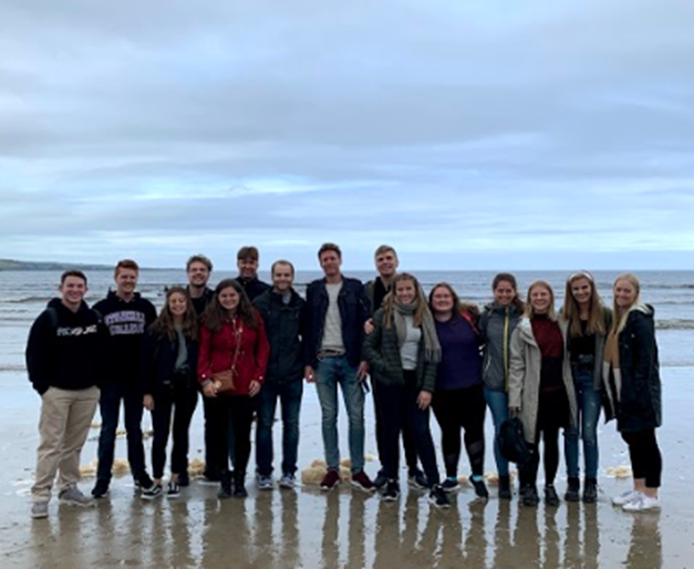 A group of people standing on a beach posing for the camera  Description automatically generated